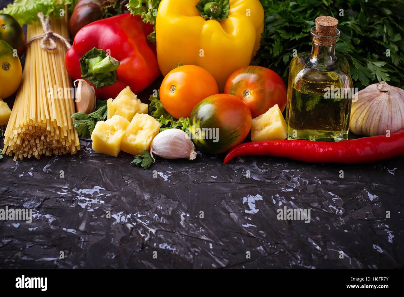 Concepto de comida italiana. Pasta, aceite de oliva, tomate, pimiento, perejil y queso. El enfoque selectivo. Imagen De Stock