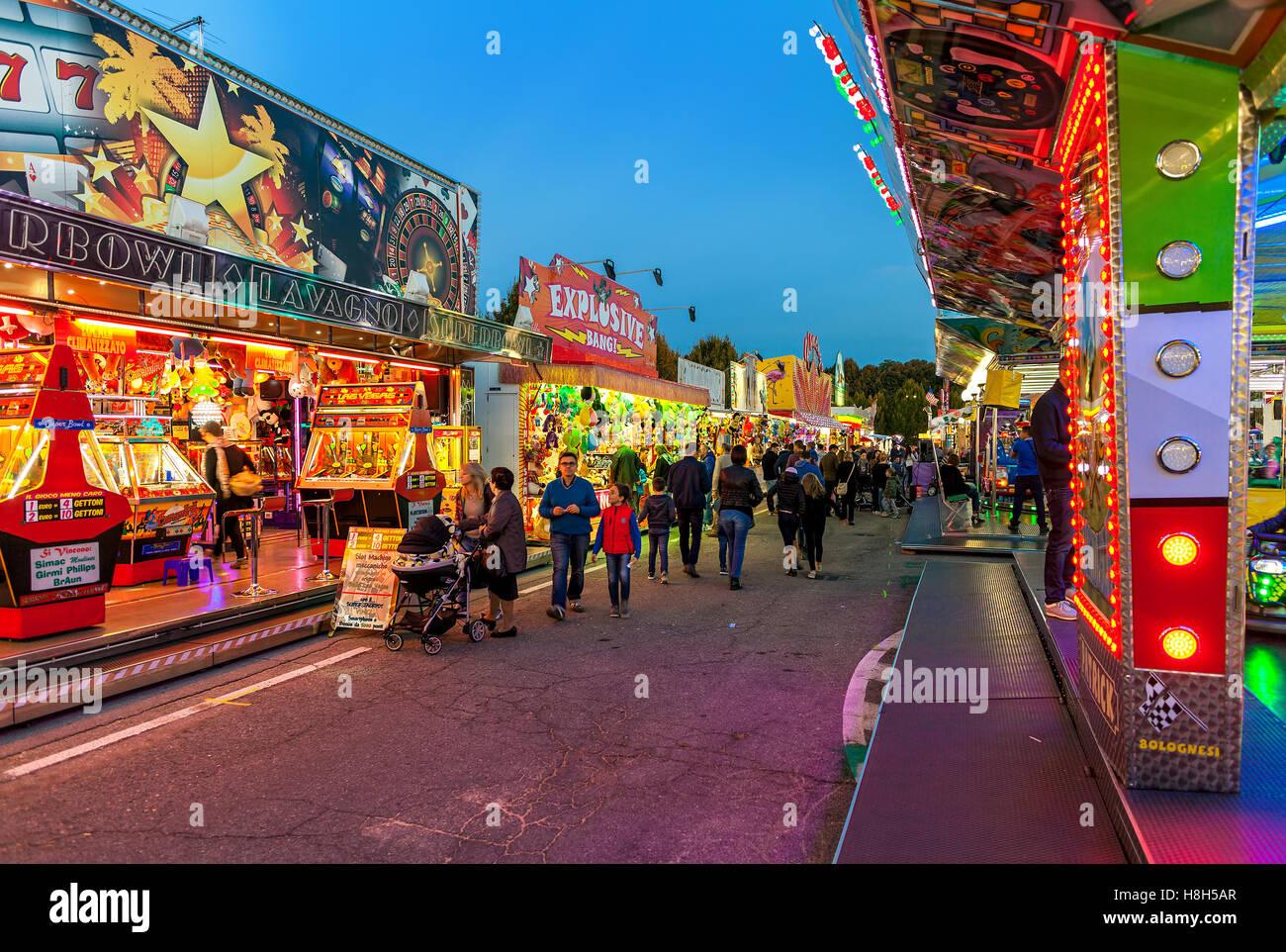 La gente caminando por el iluminado se cala y atracción en el Luna Park, en Alba, Italia. Imagen De Stock