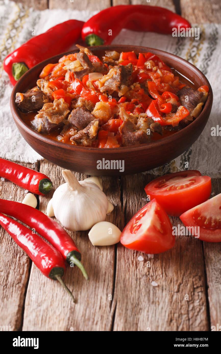 El guiso de cordero con cebolla, tomate y pimiento en un tazón de cerca en la tabla vertical. Imagen De Stock
