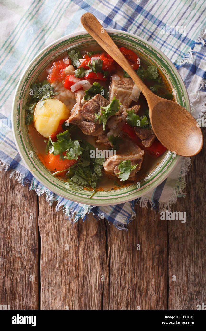 Shurpa cordero sopa con verduras closeup al plato en la mesa. Vista vertical desde arriba Imagen De Stock