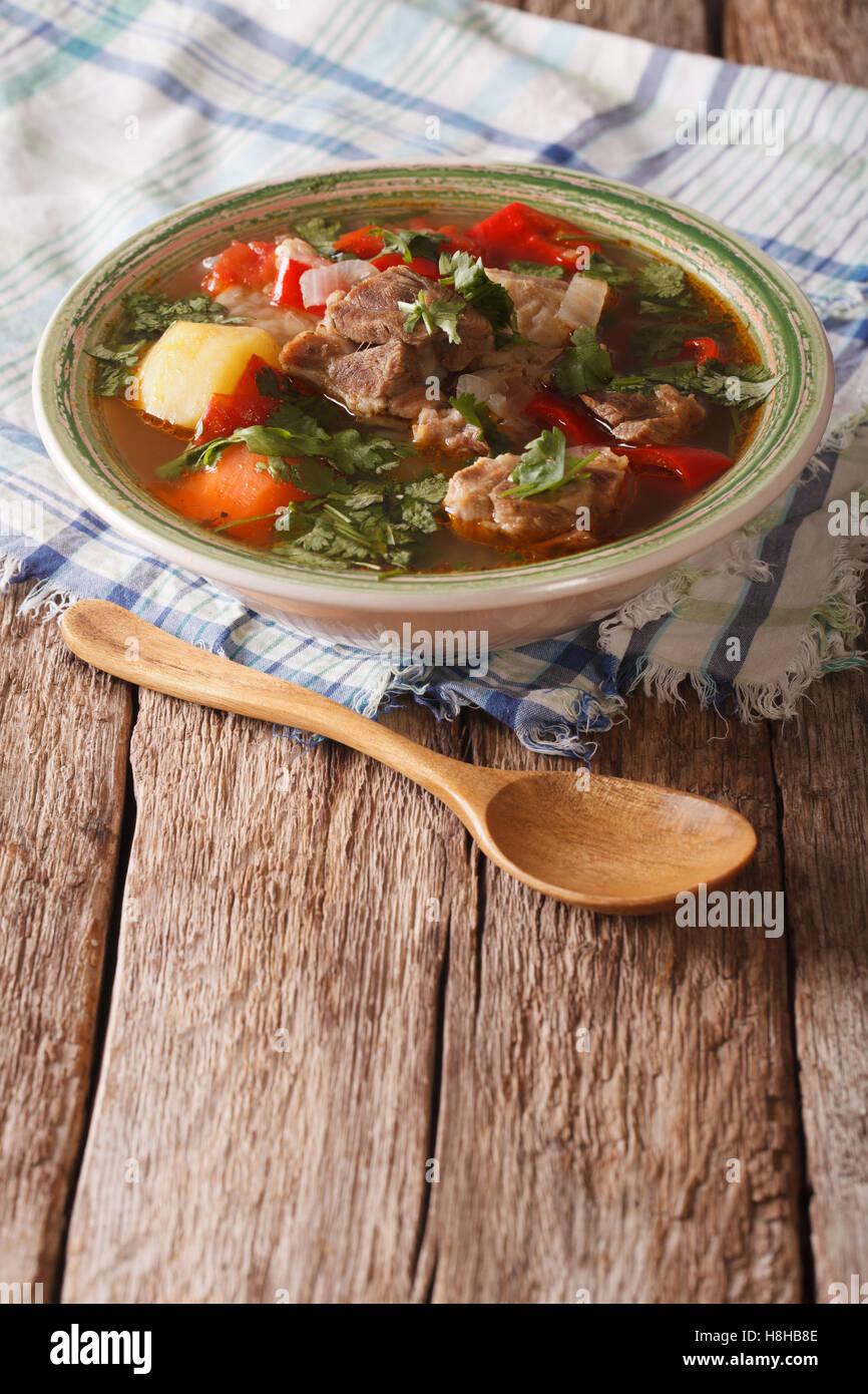 Shurpa cordero sopa con verduras closeup en la placa vertical sobre la mesa. Imagen De Stock