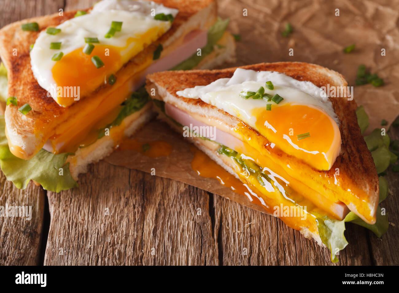 Cortar sandwich con huevo frito, jamón y queso de cerca en el papel sobre la mesa horizontal. Imagen De Stock