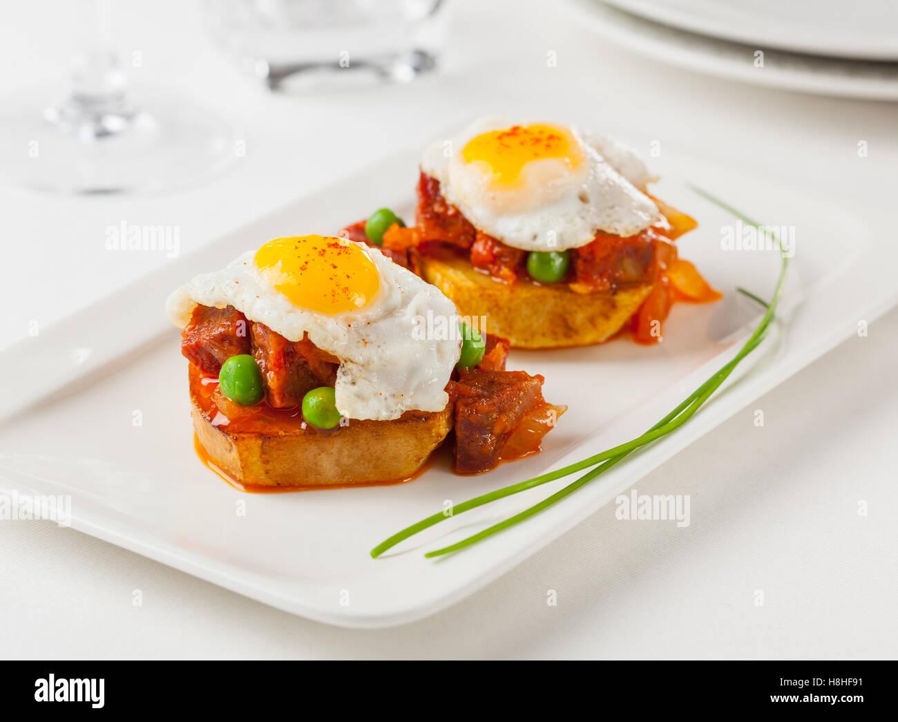 Chorizo y huevo frito sobre una rodaja de patata. Pequeña placa de tapas para compartir. Imagen De Stock