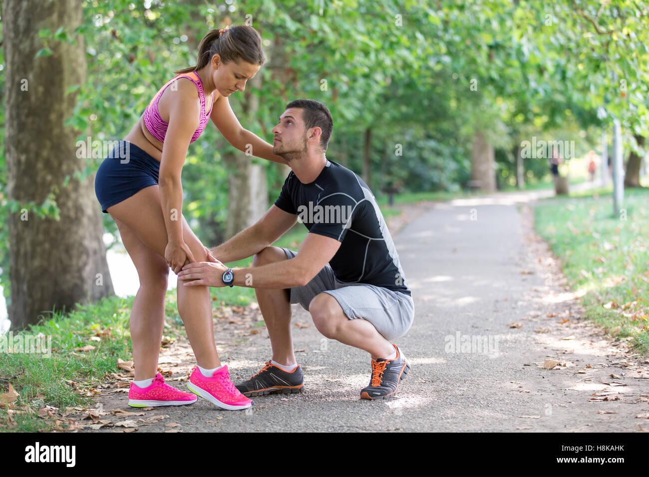 El hombre ayuda a la mujer con la rodilla lesionada en la actividad deportiva Foto de stock