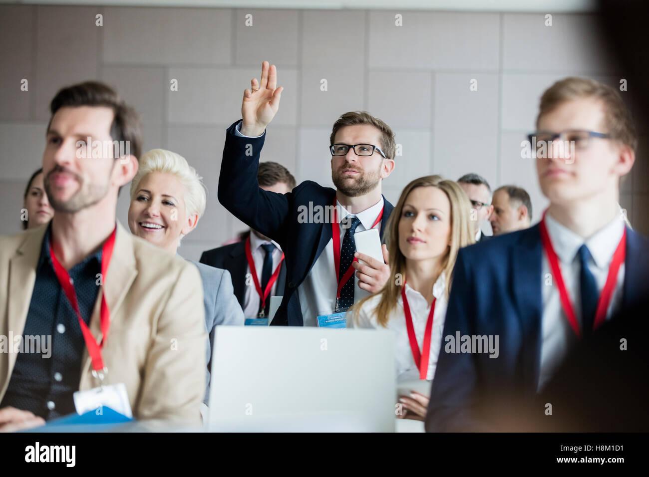 Empresario levantando la mano durante el seminario en el centro de convenciones Imagen De Stock