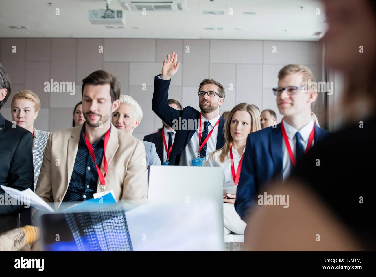 Empresario levantando la mano durante el seminario Imagen De Stock