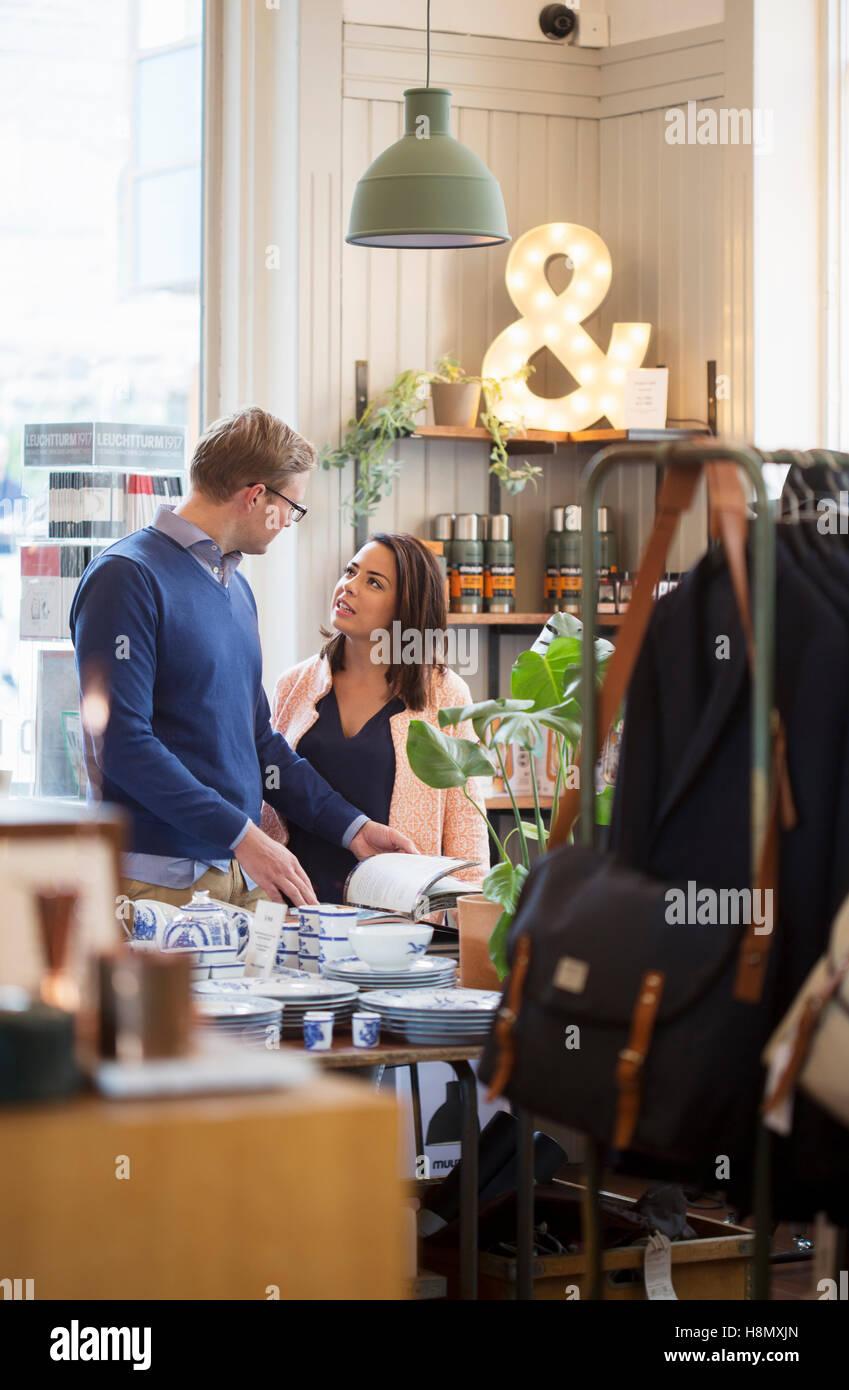 Pareja joven hablando en la tienda Foto de stock