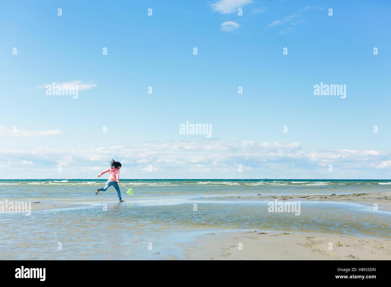 Chica (10-11) que se ejecutan en la playa Imagen De Stock