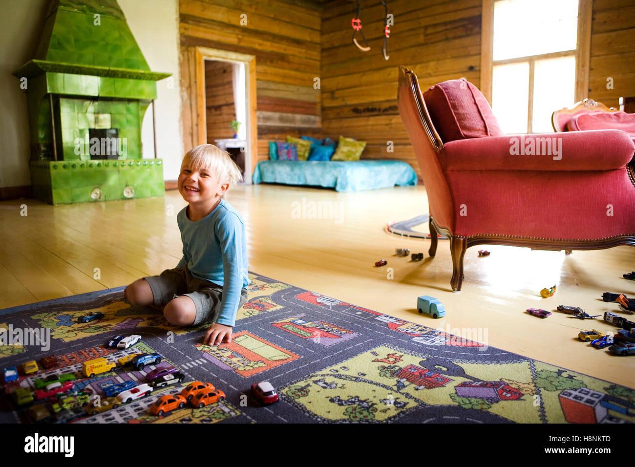 Boy (4-5) de rodillas sobre la alfombra multicolor en la habitación Imagen De Stock