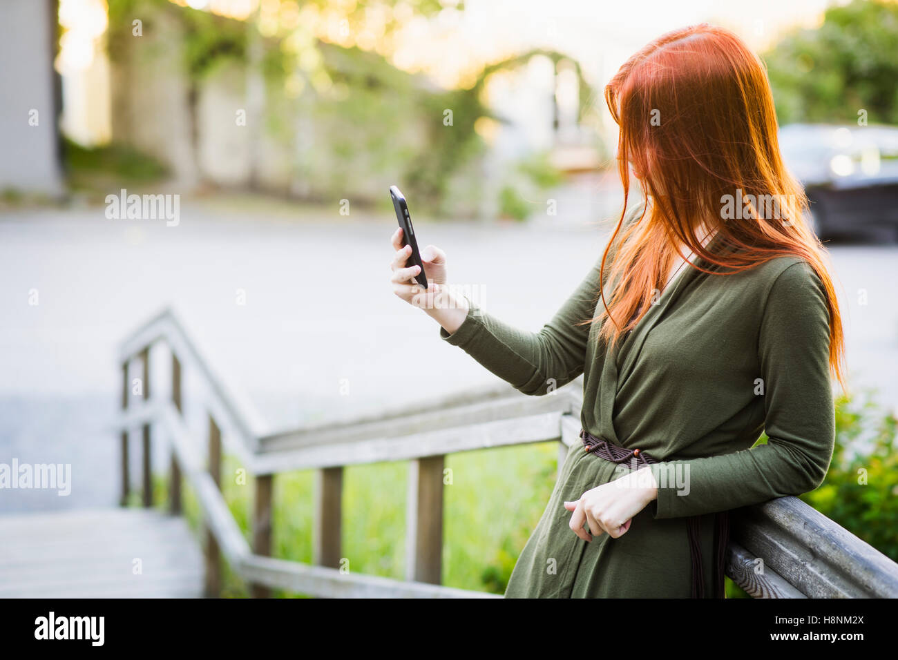 Redhaired Mujer de pie sobre la escalera y utilizando el teléfono Imagen De Stock