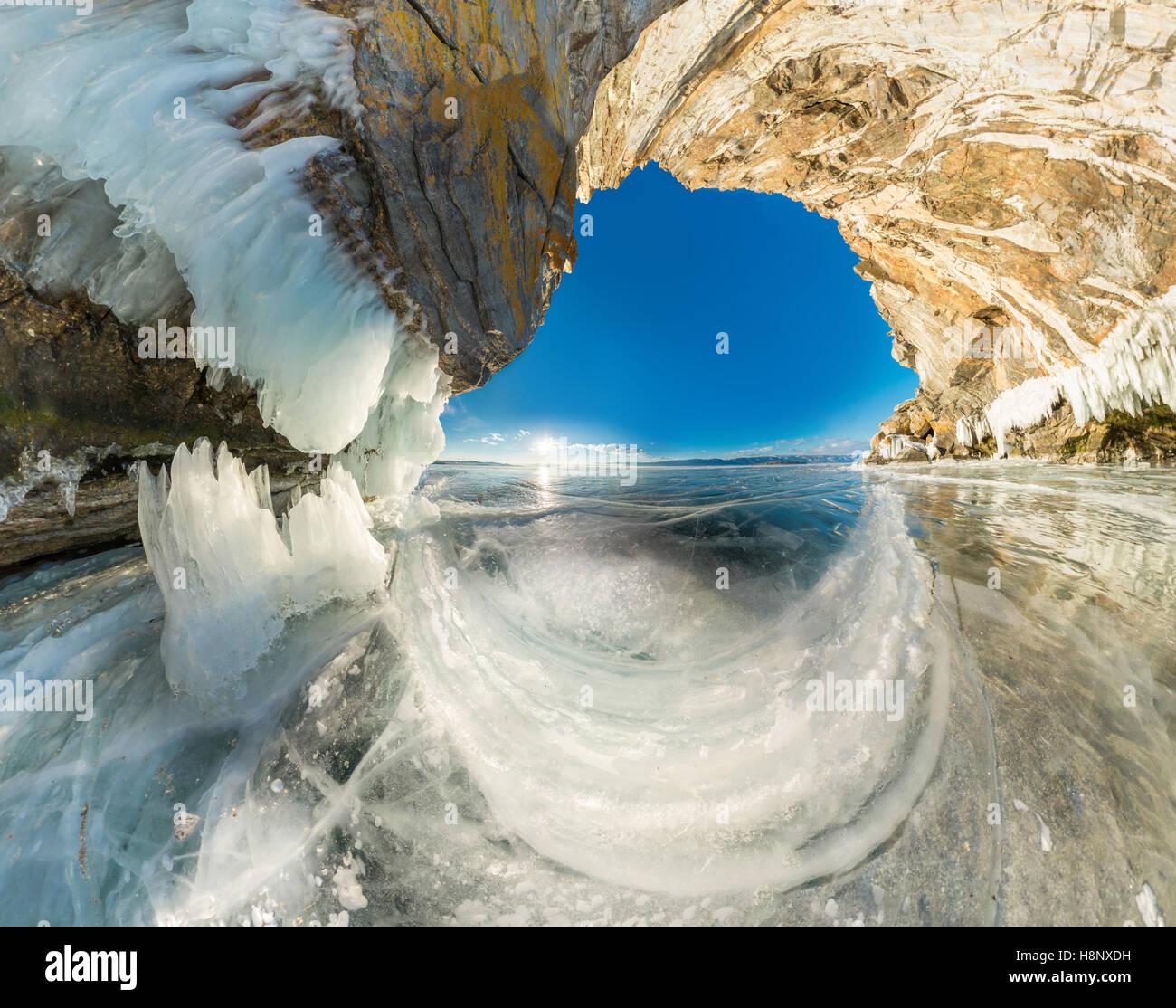 La gruta de hielo en la roca de Olkhon isla en el Lago Baikal cubierto de hielo de ángulo amplio panorama. Foto de stock