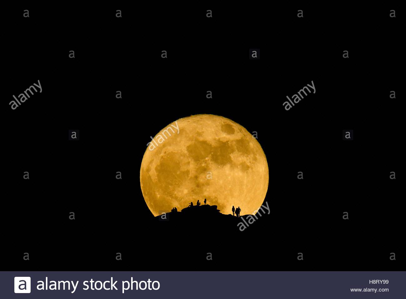 Observar a la gente como el Super Luna sube por las montañas Catalina al norte de Tucson, Arizona, el 14 de Imagen De Stock
