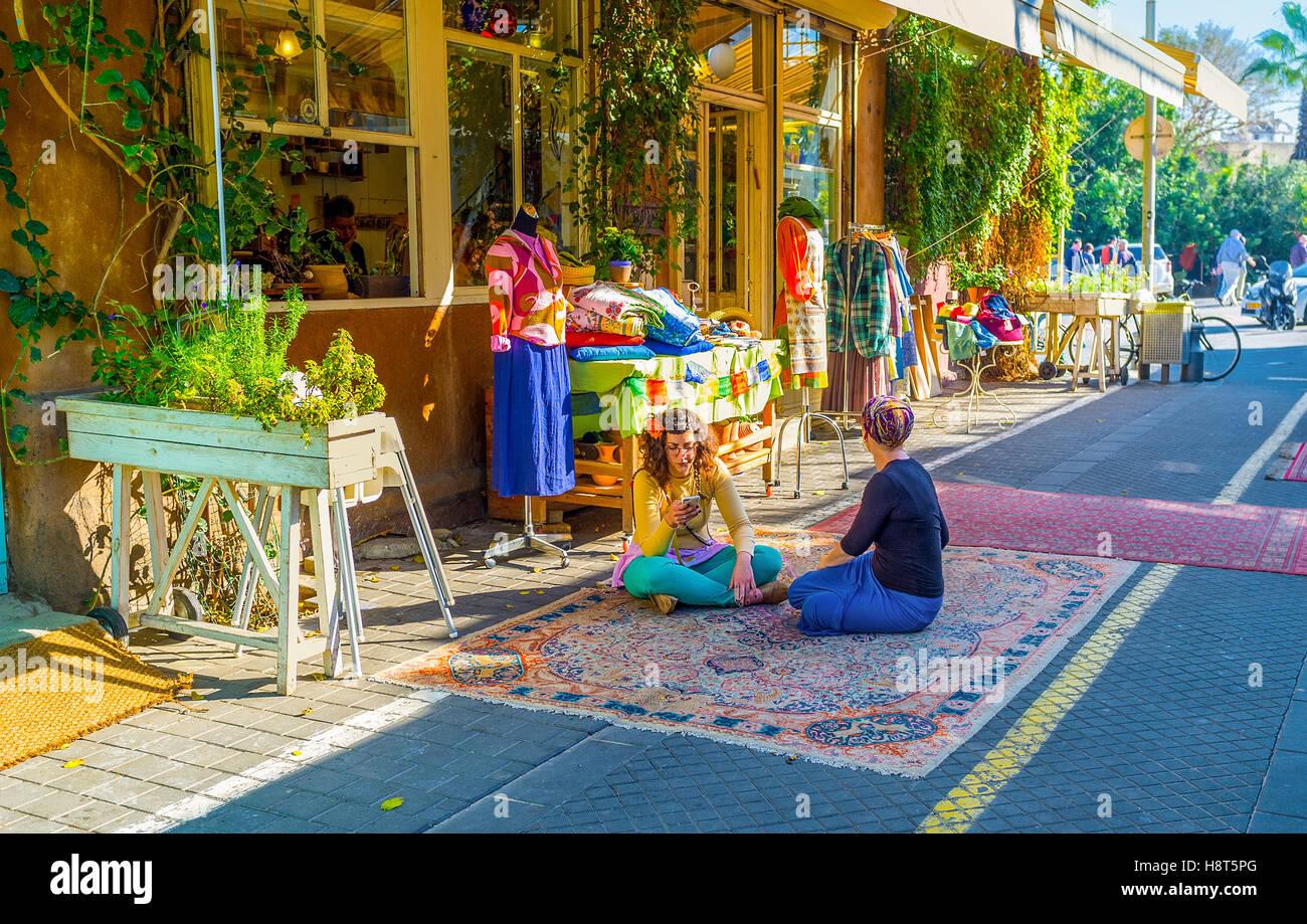 Los vendedores de ropa taller sentarse con las piernas cruzadas sobre la  alfombra en Market Street db2bc960145