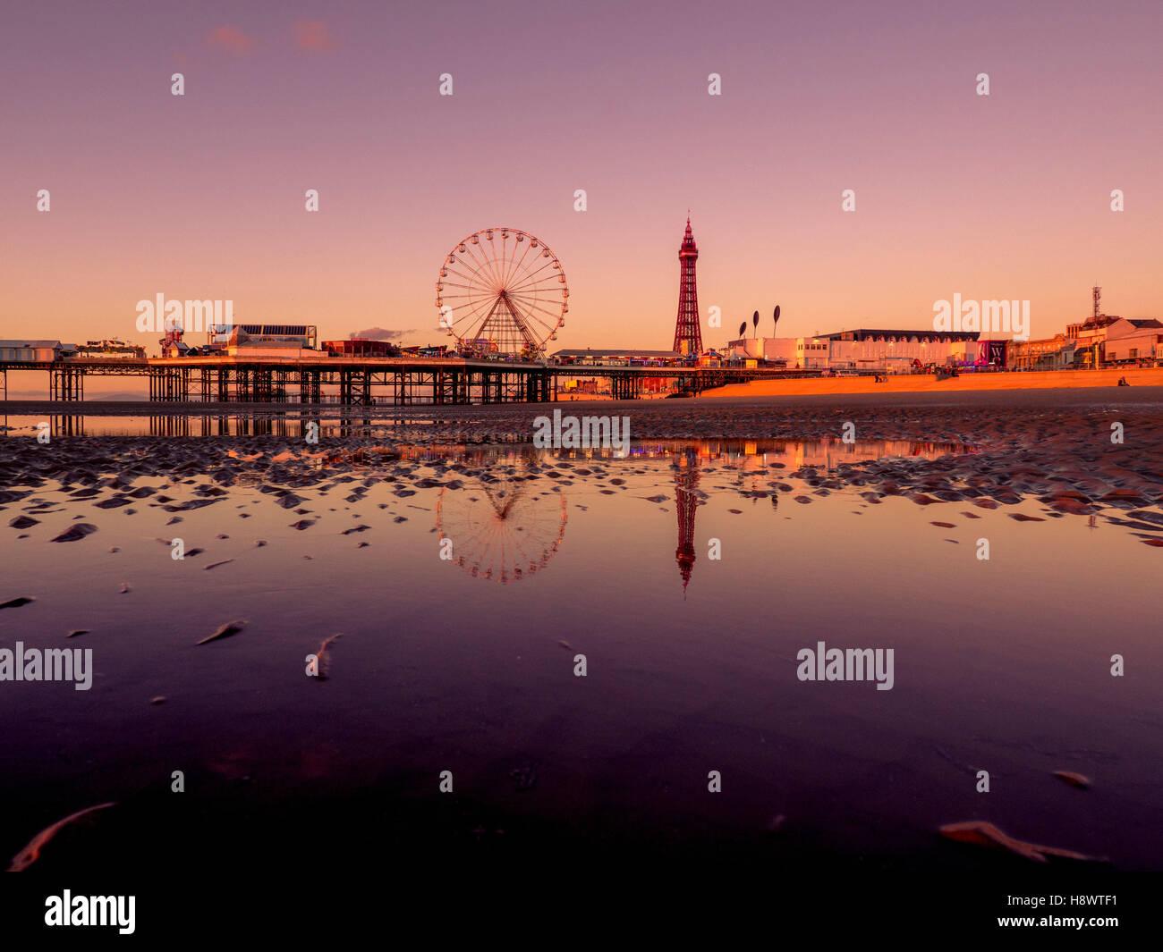 La torre de Blackpool y Central Pier con reflejo en el agua en la playa al anochecer, Lancashire, Reino Unido. Foto de stock