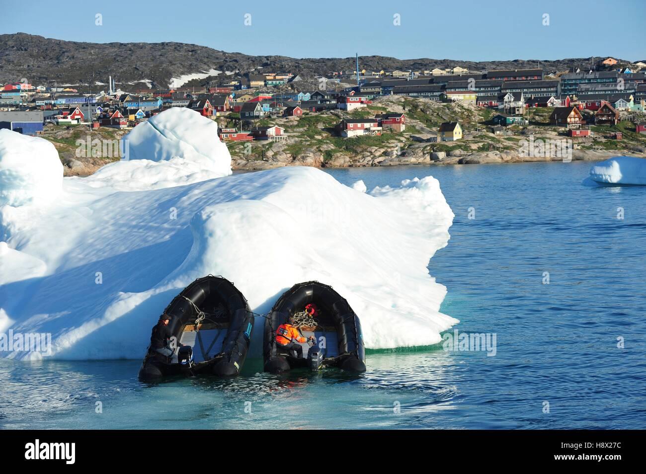 Dinamarca. Groenlandia. Costa oeste. Zodiacs empujando un iceberg para liberar a la entrada del puerto de Ilulissat. Foto de stock