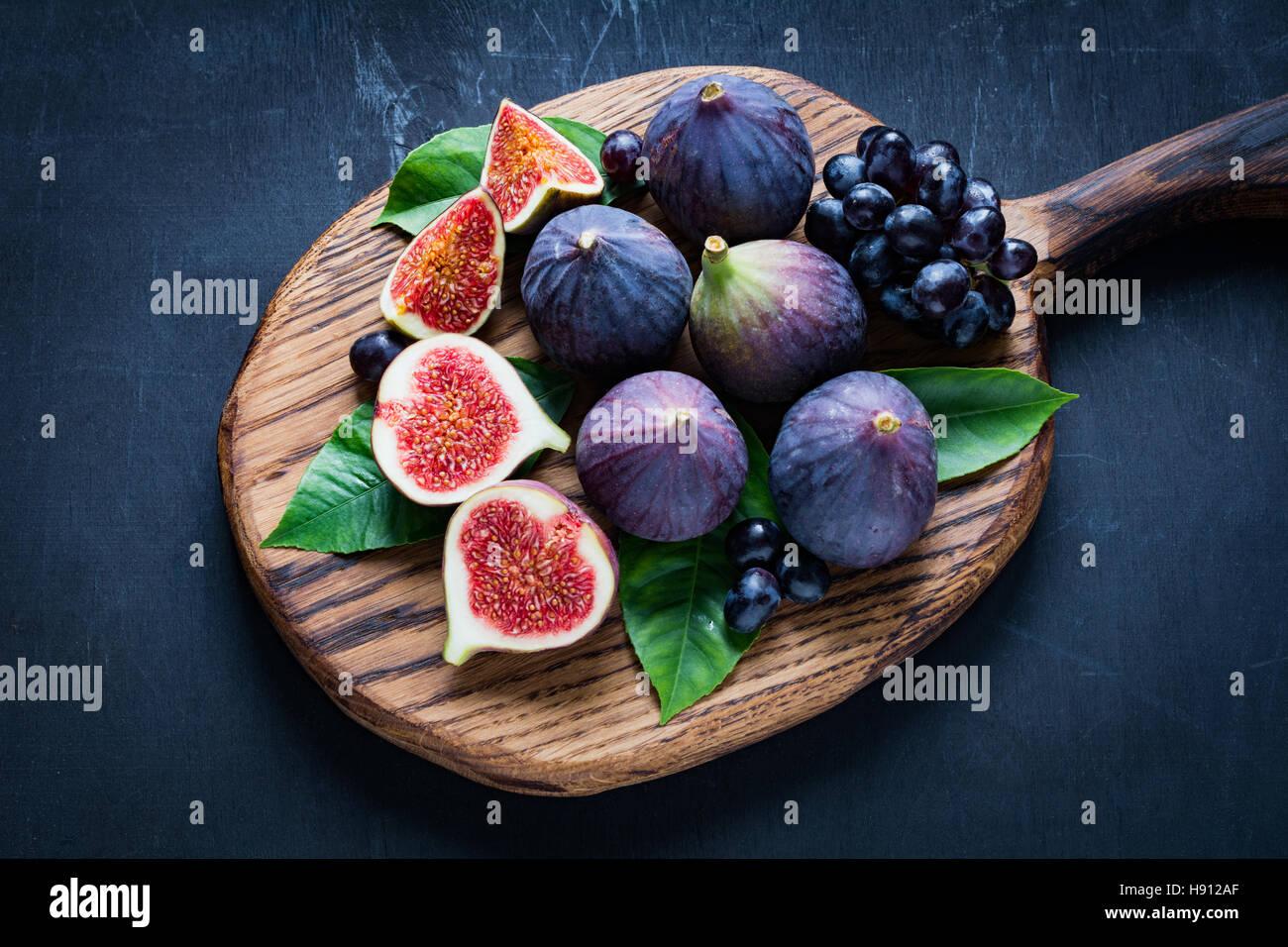 Plato de frutas: higos frescos y uvas negras 'Isabella' en la tabla de cortar de madera. Vista horizontal Imagen De Stock