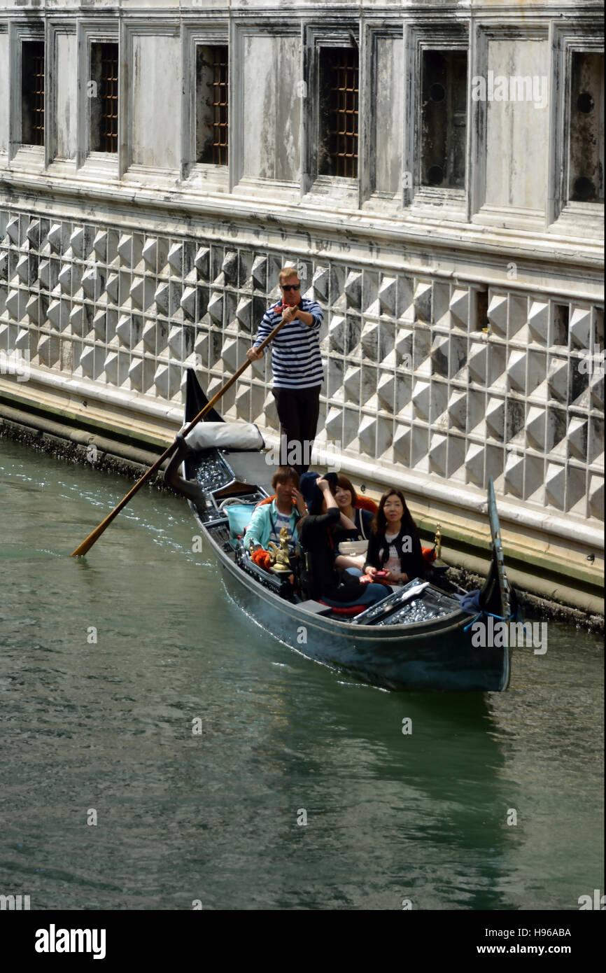 Góndola con turistas y gondolero en un canal de Venecia. Imagen De Stock