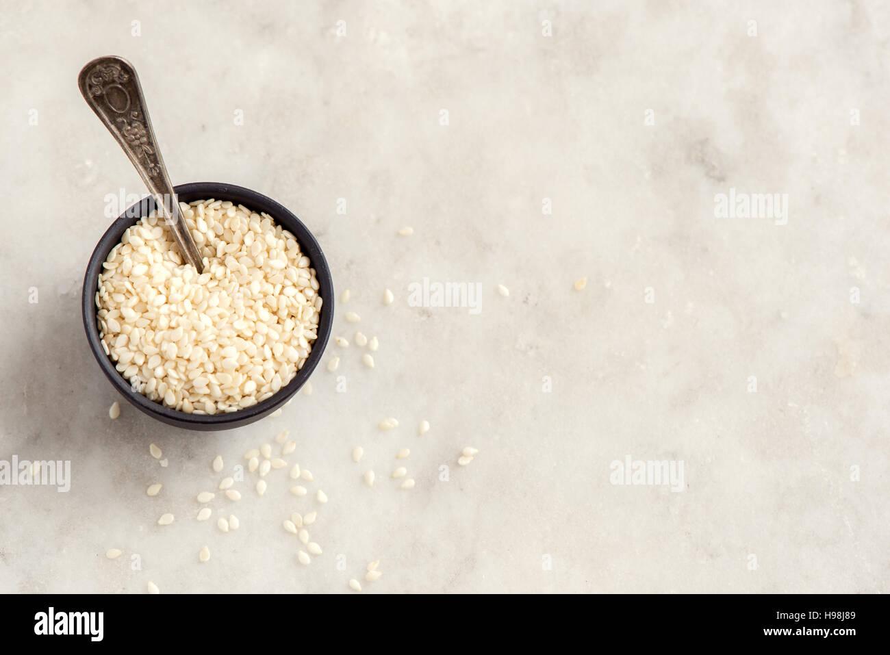 Las semillas de sésamo en un tazón de piedra blanca sobre fondo con copia espacio - ingrediente alimentario Imagen De Stock