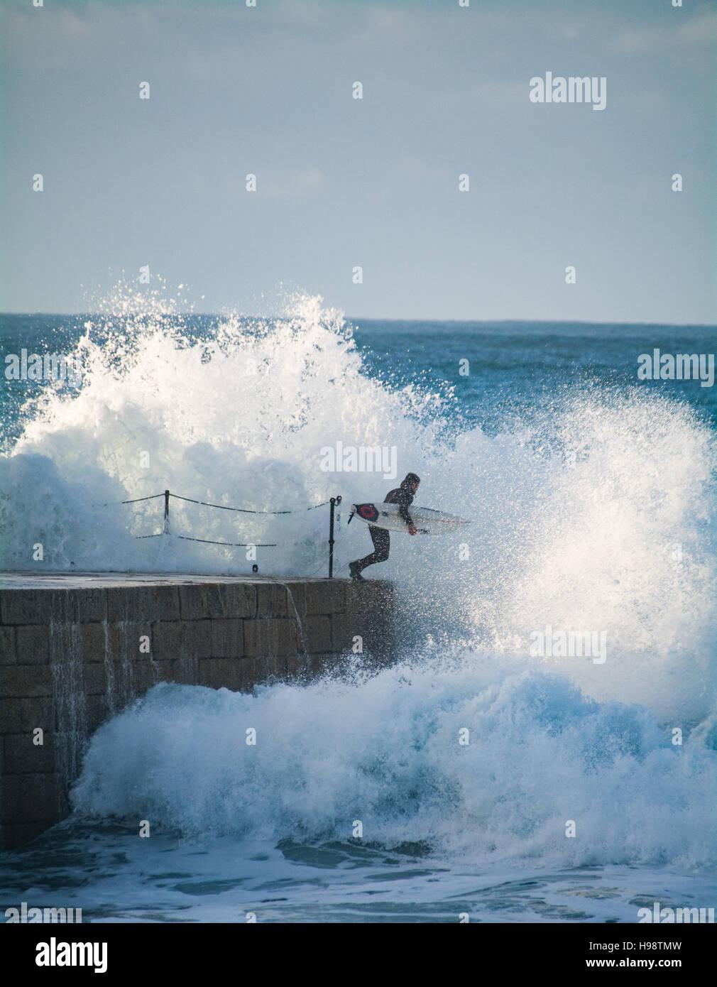 Porthleven, Cornualles, en el Reino Unido. 20 de noviembre de 2016. El clima del Reino Unido. Los surfistas teniendo arriesgada en ruta hacia el mar después de la tormenta Porthleven Angus pasa de Cornualles. El espigón en el puerto de entrada está normalmente cerrada durante un tiempo tormentoso como varias personas han sido asesinadas en el pasado por ser lavadas. Crédito: Simon Maycock/Alamy Live News Foto de stock