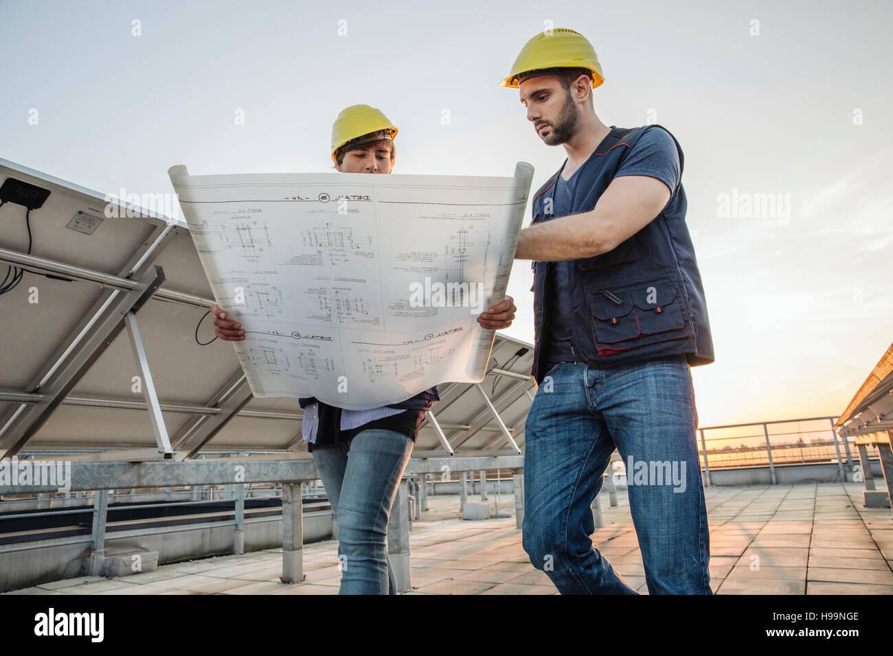Ingeniero y arquitecto inspeccionando estación de energía solar Imagen De Stock