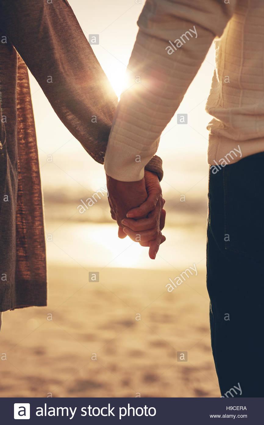 Cerrar vista trasera de una romántica pareja senior manos contra el mar al atardecer. Imagen De Stock