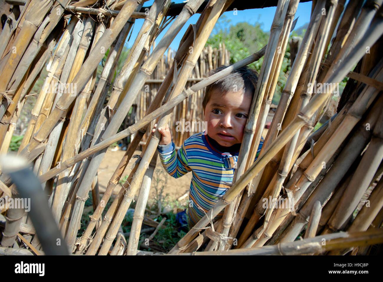 Niño indígena maya en casa en mano de Leon, pequeña aldea remota fuera Antigua, Sacatepequez, Guatemala. Imagen De Stock