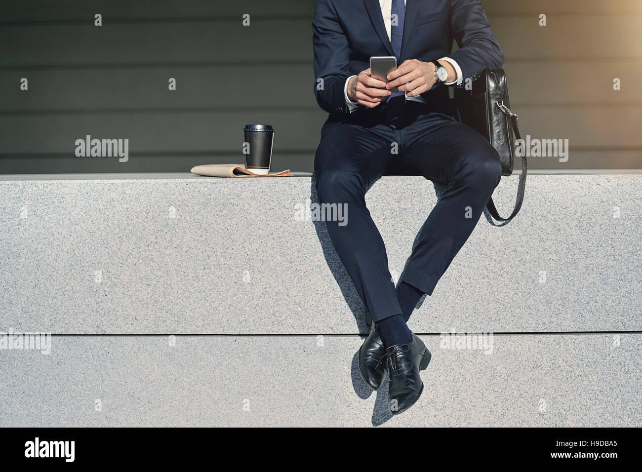 Las piernas cruzadas del empresario sentado con teléfono celular. Disparó al aire libre horizontal Foto de stock