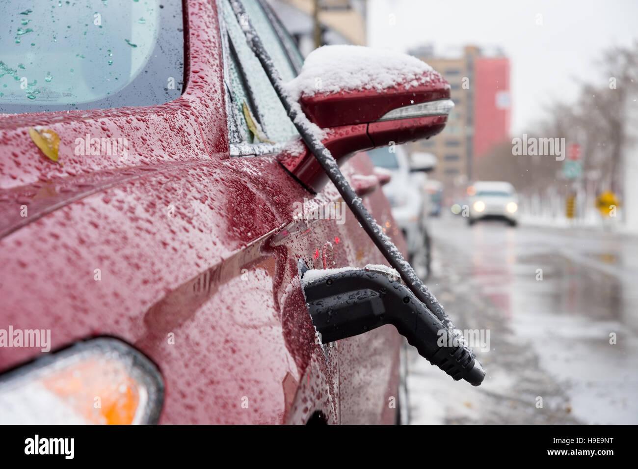 Un coche eléctrico rojo cargando en Montreal, Canadá Imagen De Stock