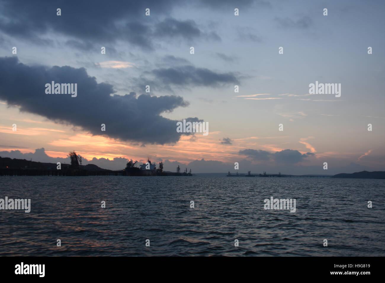 Mirando hacia el oeste por Milford Haven a las terminales de petróleo y gas con una impresionante puesta de sol de cielo azul, un resplandor rojo y algunas nubes Foto de stock