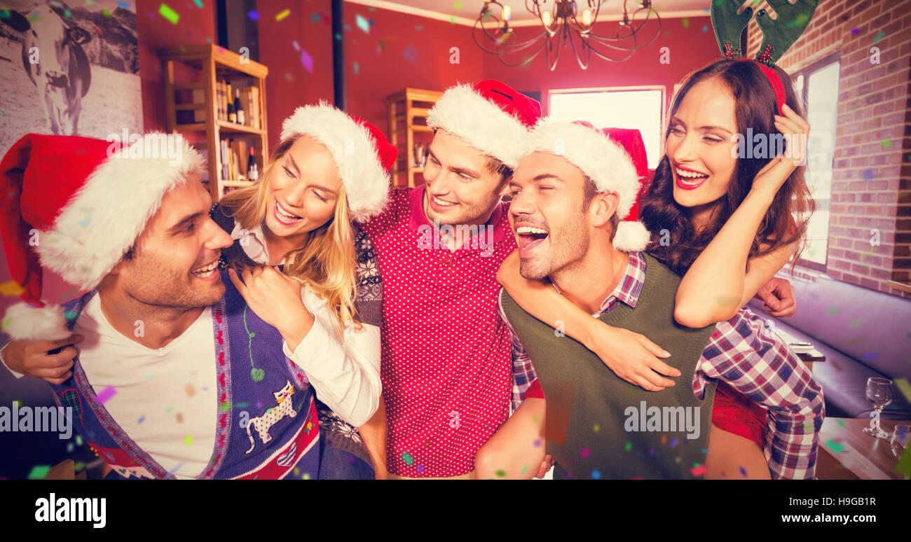 Imagen compuesta de hombres vestidos de navidad vestidos de mujer dando paseos piggyback Imagen De Stock
