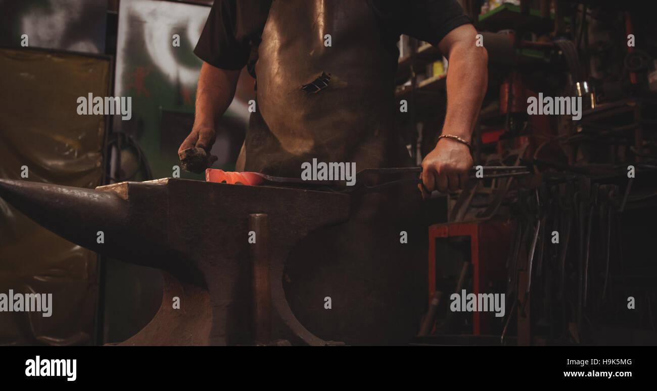Herrero trabajando en metal caliente utilizando un martillo para dar forma Imagen De Stock
