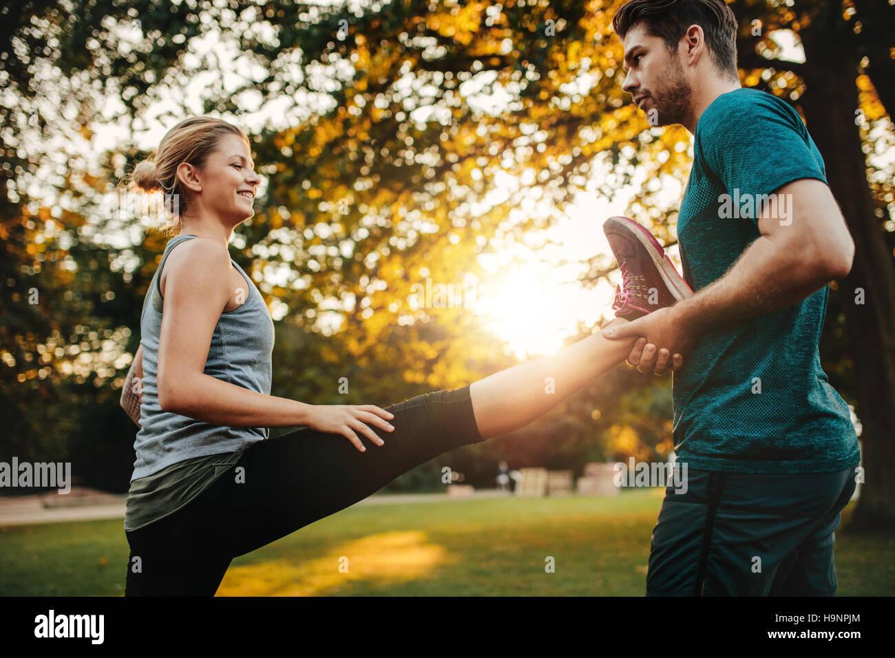 Entrenador personal manteniendo la pierna de mujer estiramiento en park. Ejercicio femenino con el apoyo de su entrenador. Imagen De Stock