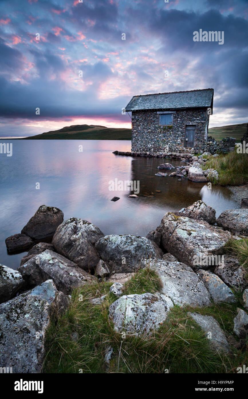 Atardecer de verano sobre el antiguo cobertizo en Devoke agua, Lake District. Imagen De Stock