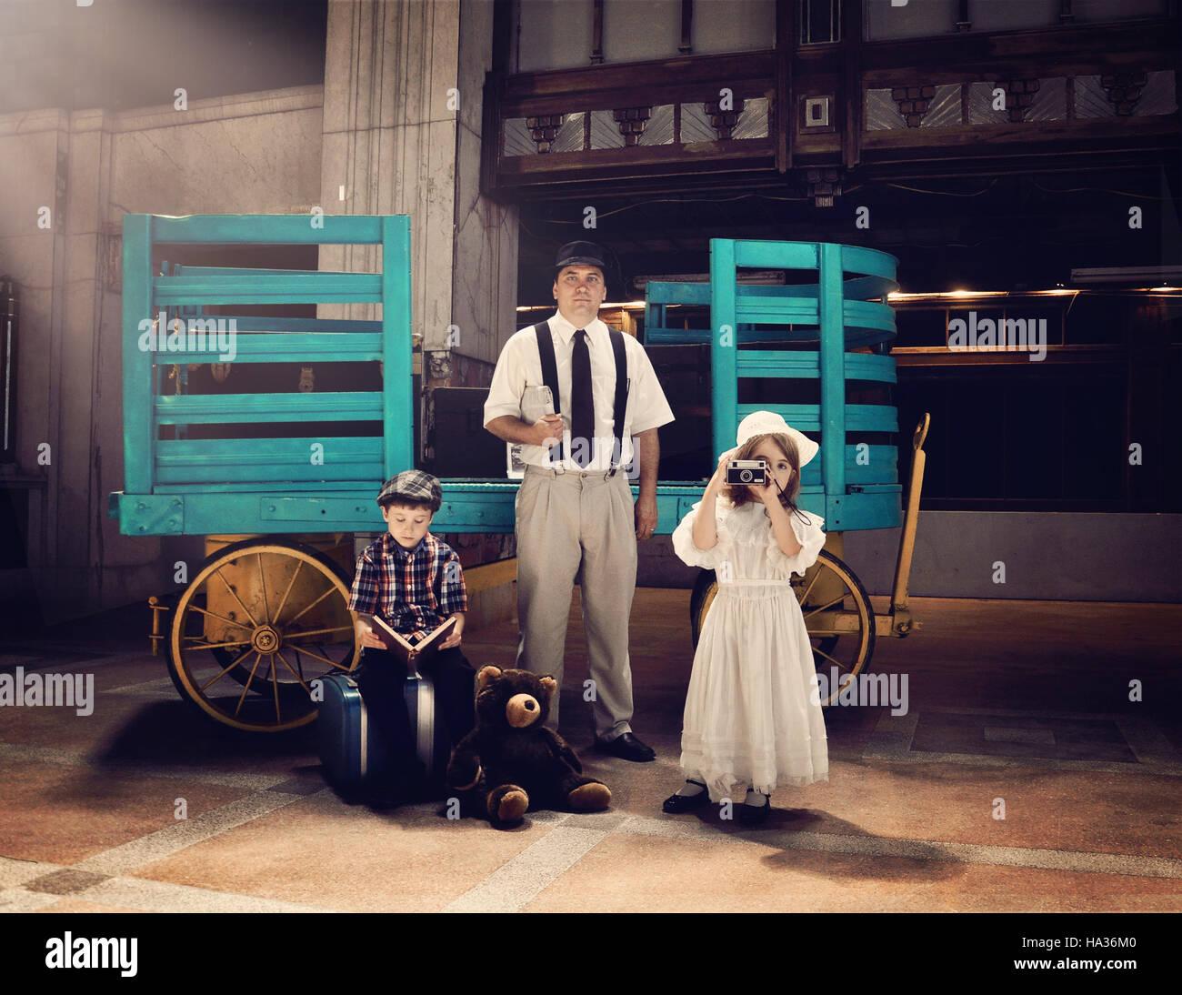 Una antigua familia vintage está esperando en una vieja estación de tren por un carrito de equipaje para el concepto de viaje o de vacaciones. Foto de stock