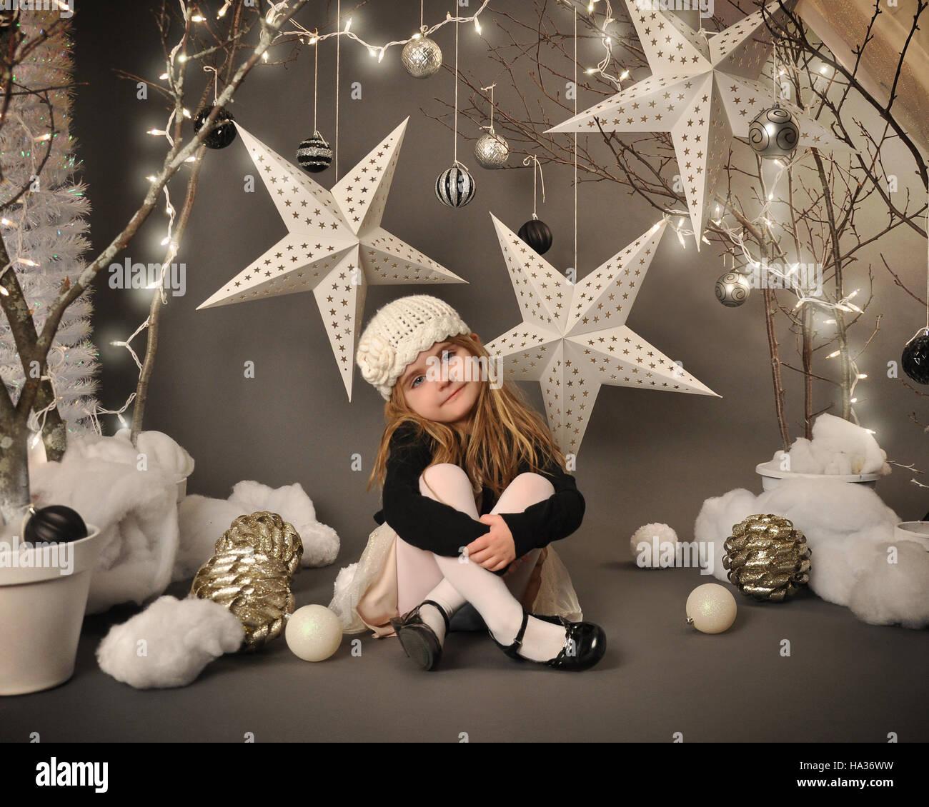 Una niña pequeña está sentada en un país de las maravillas invernal setip con árboles, estrellas colgantes y luces de Navidad alrededor del fondo para una temporada o vacaciones con Foto de stock