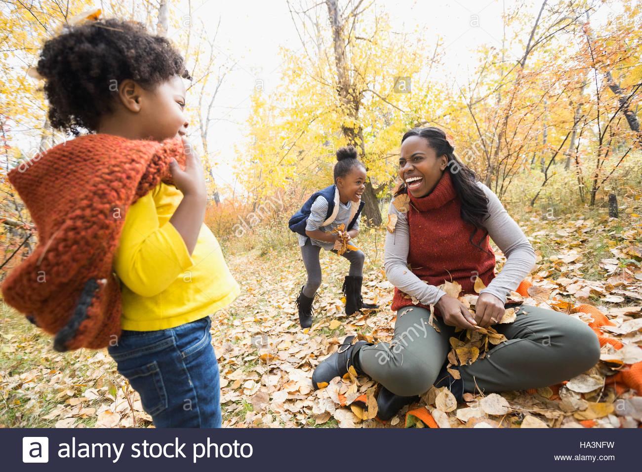 Madre y sus hijas jugando a arrojar hojas de otoño en el parque Imagen De Stock