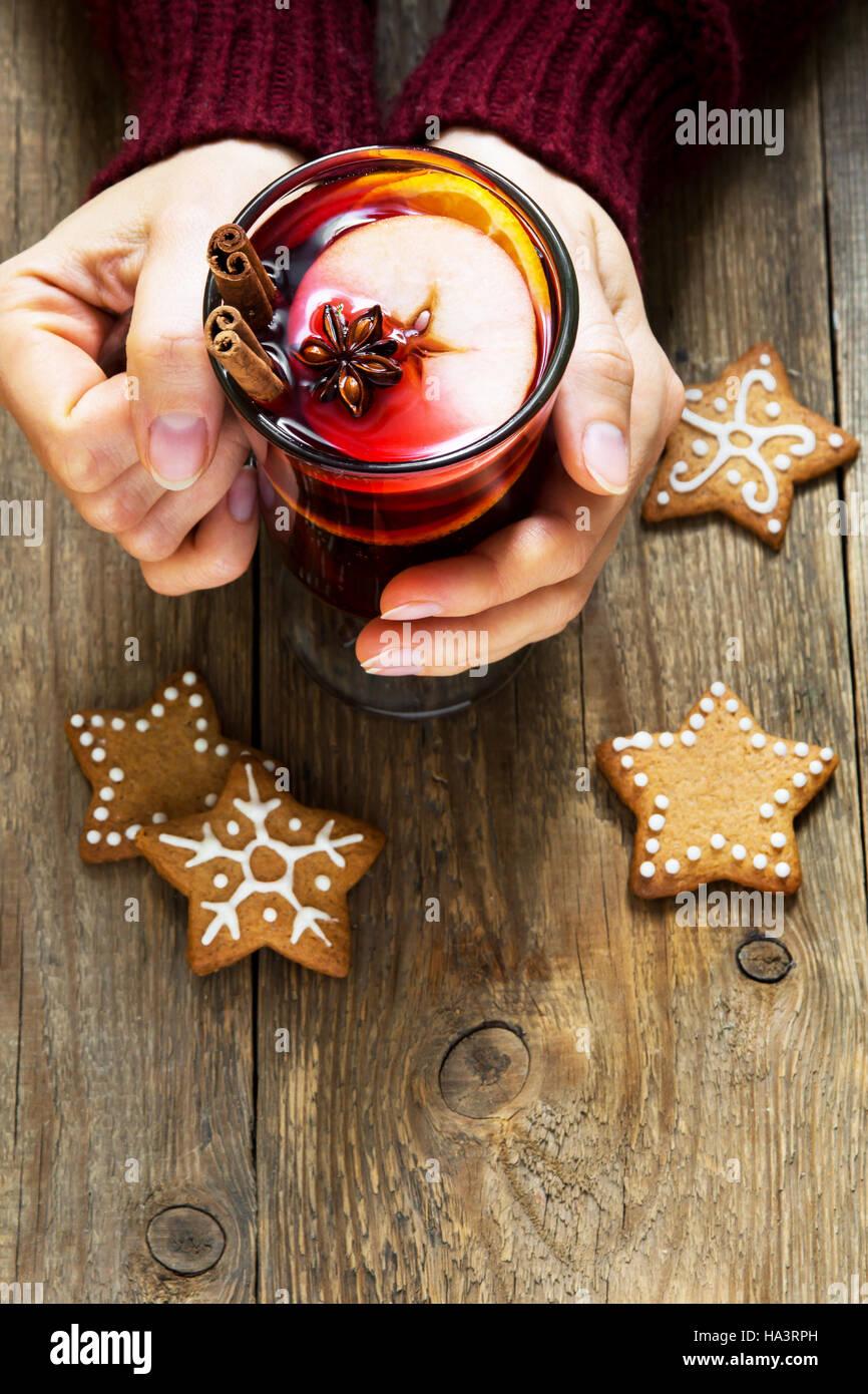Bebida caliente de Navidad - en manos femeninas, vino especiado con canela, anís y jengibre navideños Imagen De Stock