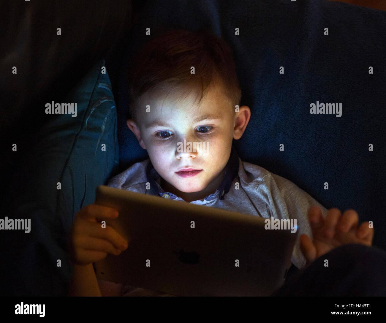 Joven sentada con Apple ipad para acceder a Internet mediante tecnología inalámbrica. Imagen De Stock
