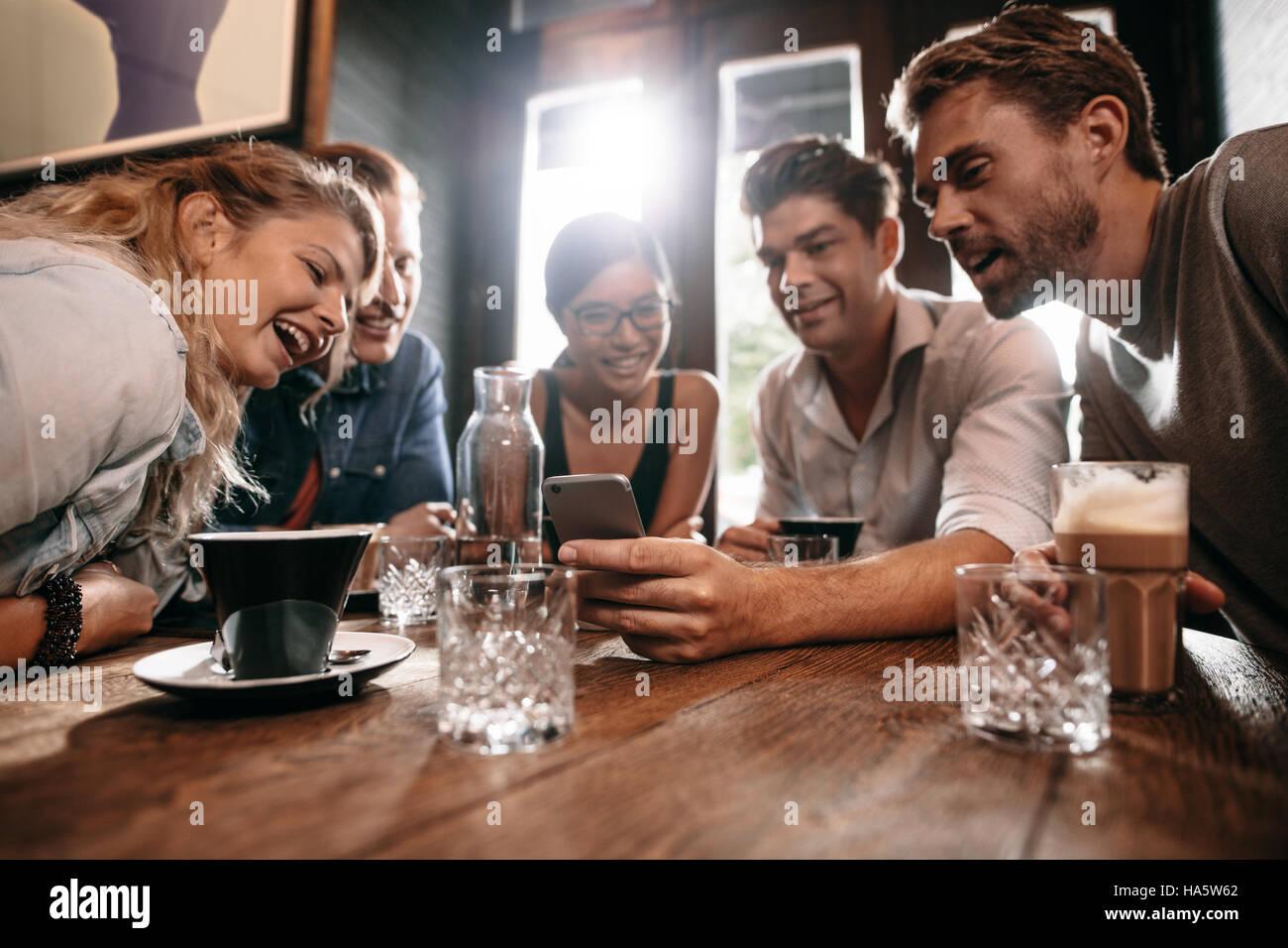 Jóvenes amigos mirando teléfono inteligente mientras está sentado en la cafetería. Mestizos Imagen De Stock