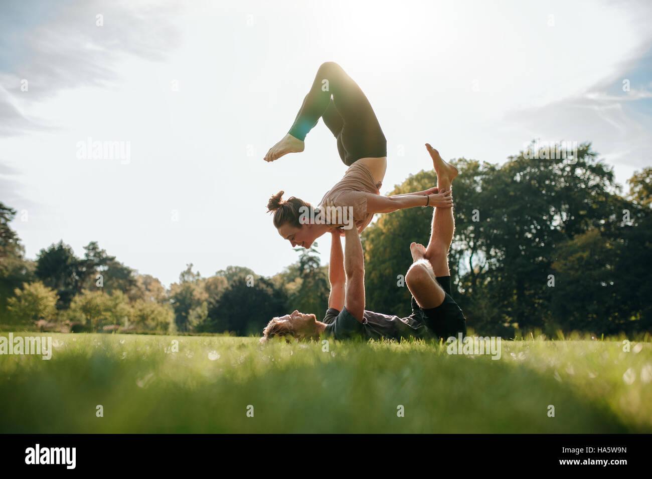 Caucasian par hacer acro yoga en el parque. El hombre y la mujer haciendo varias posturas de yoga par afuera. Imagen De Stock