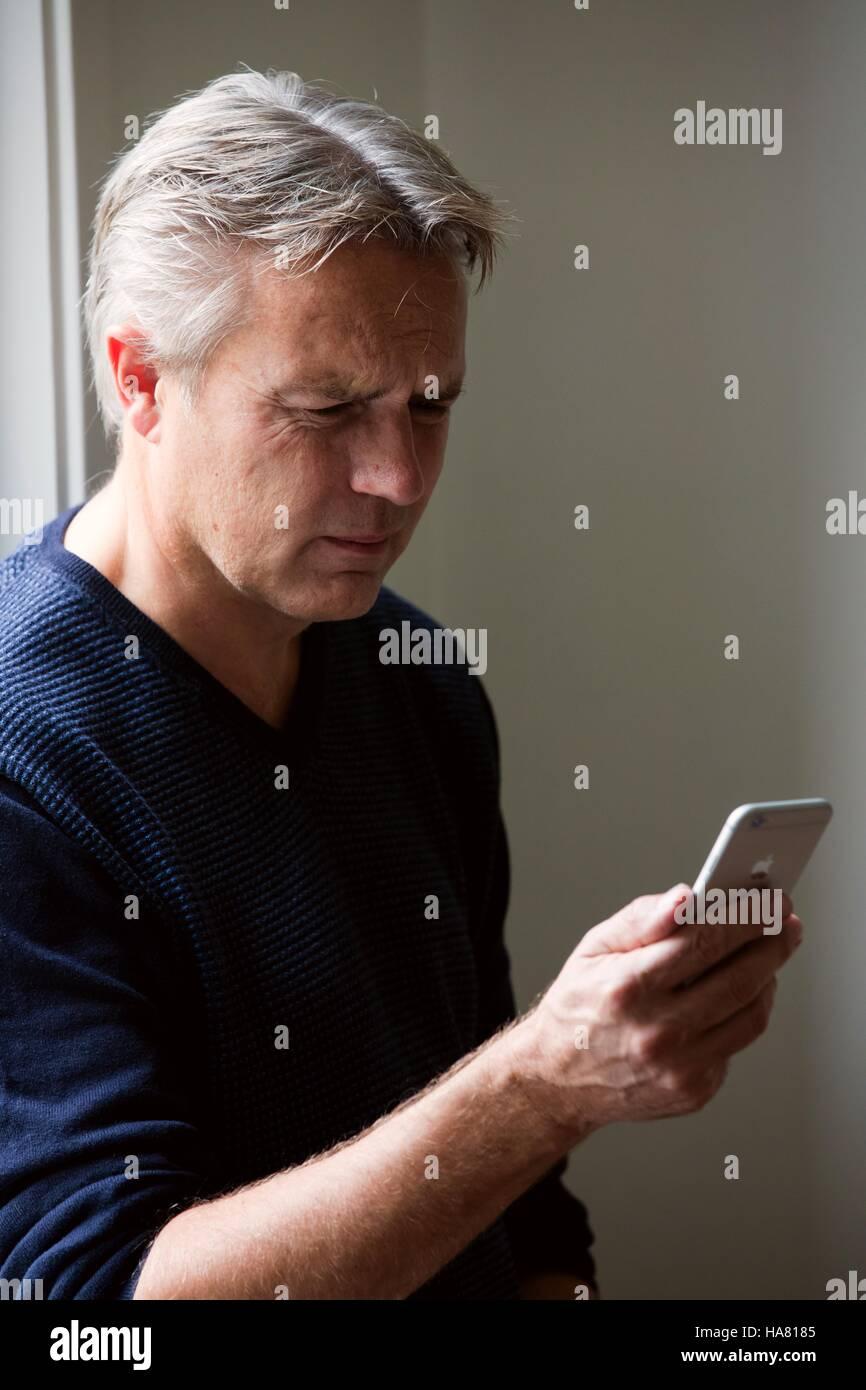 Hombre adulto mirando preocupado a su teléfono celular Imagen De Stock