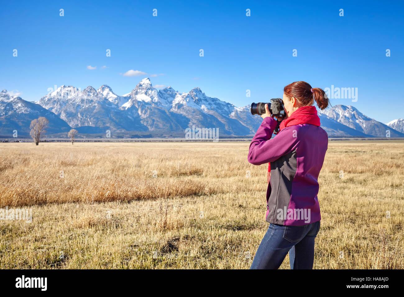 Colocar hembra excursionista tomar fotografías con la cámara DSLR en el parque nacional Grand Teton, Wyoming, Imagen De Stock