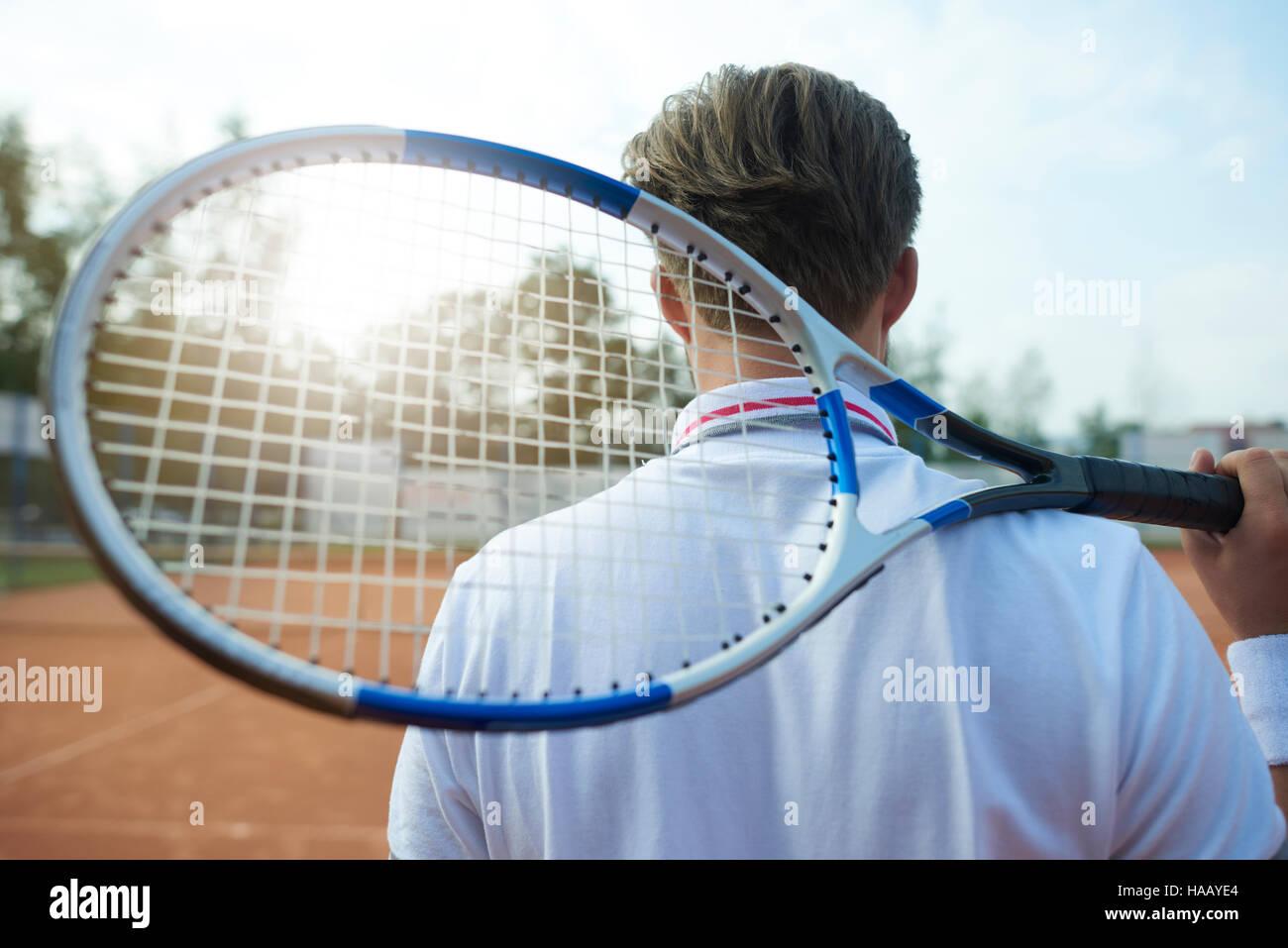 El hombre es la celebración de una raqueta de tenis Imagen De Stock
