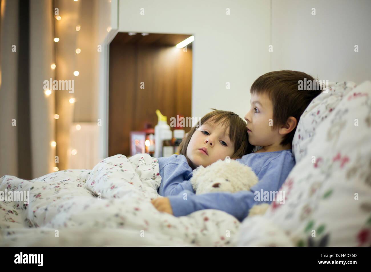Dos lindos hijos, niños enfermos, permanecer en cama con fiebre, jugando con osito de peluche Foto de stock
