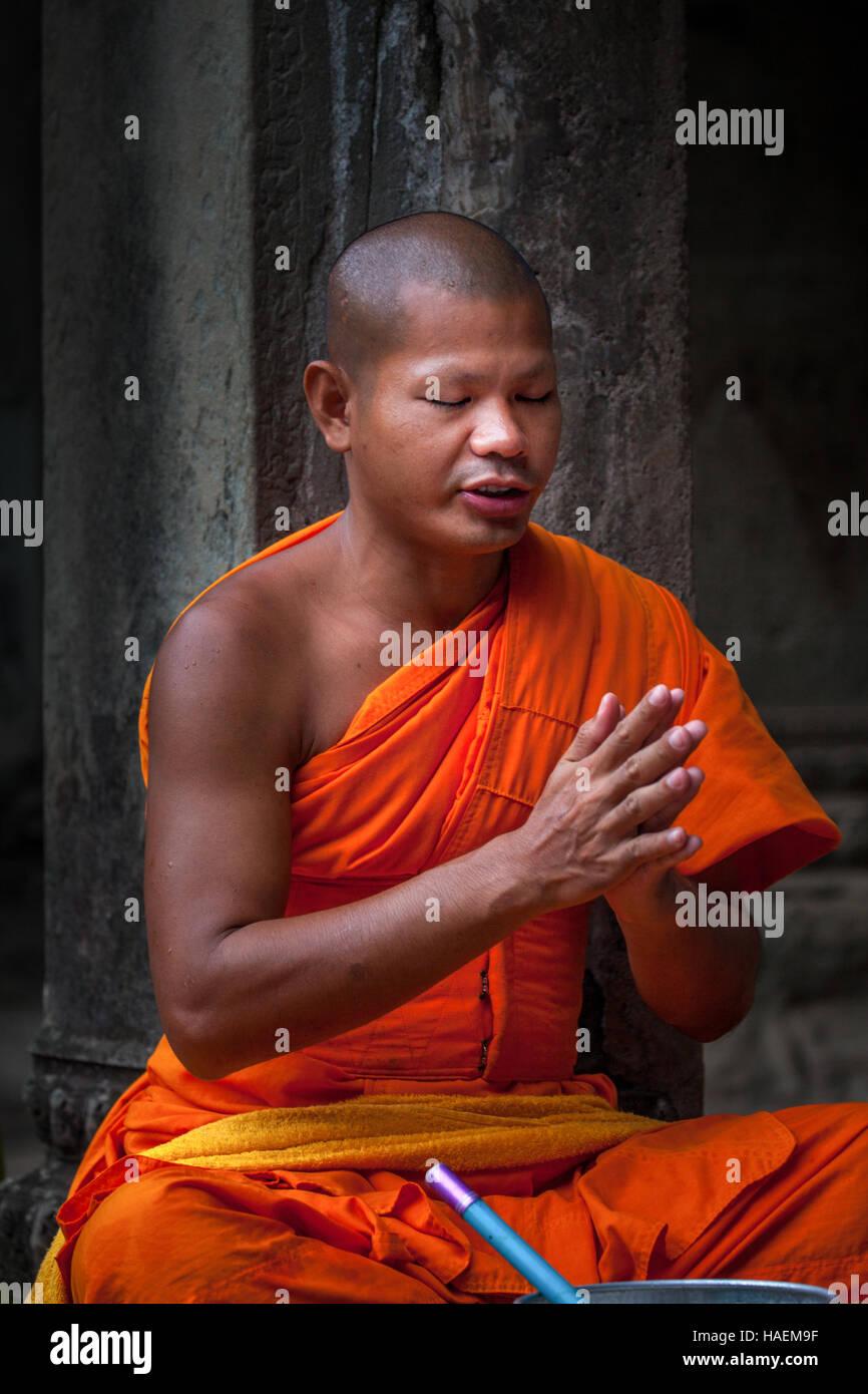 Un monje budista se sienta con las manos entrelazadas y los ojos cerrados cantando plegarias en el antiguo templo Foto de stock