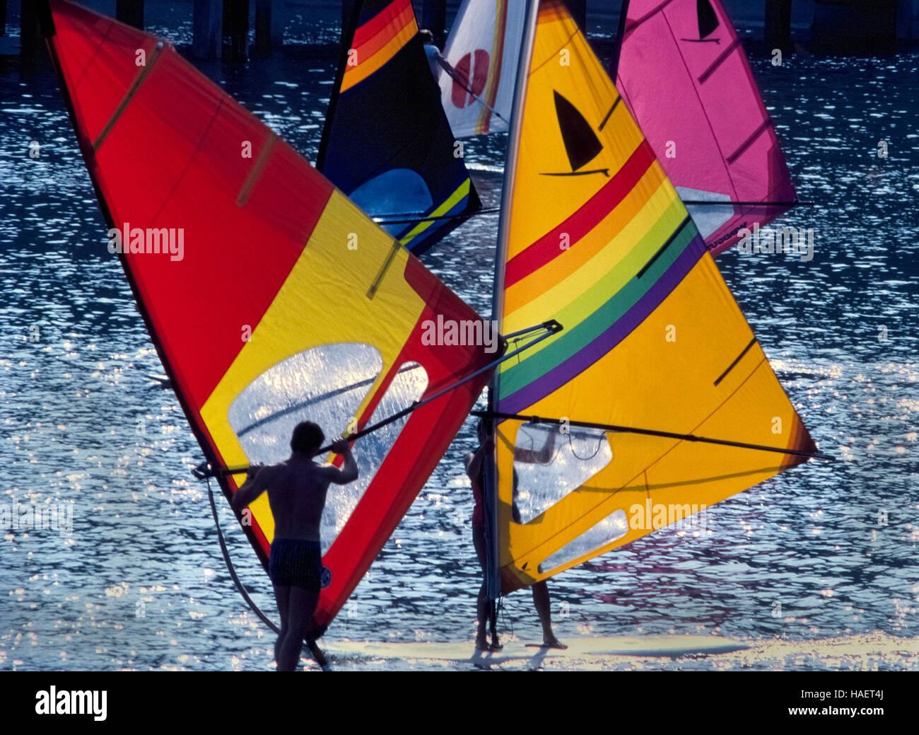 Los jóvenes windsurfistas cruzan mientras practican maniobras técnicas para este popular deporte acuático Imagen De Stock