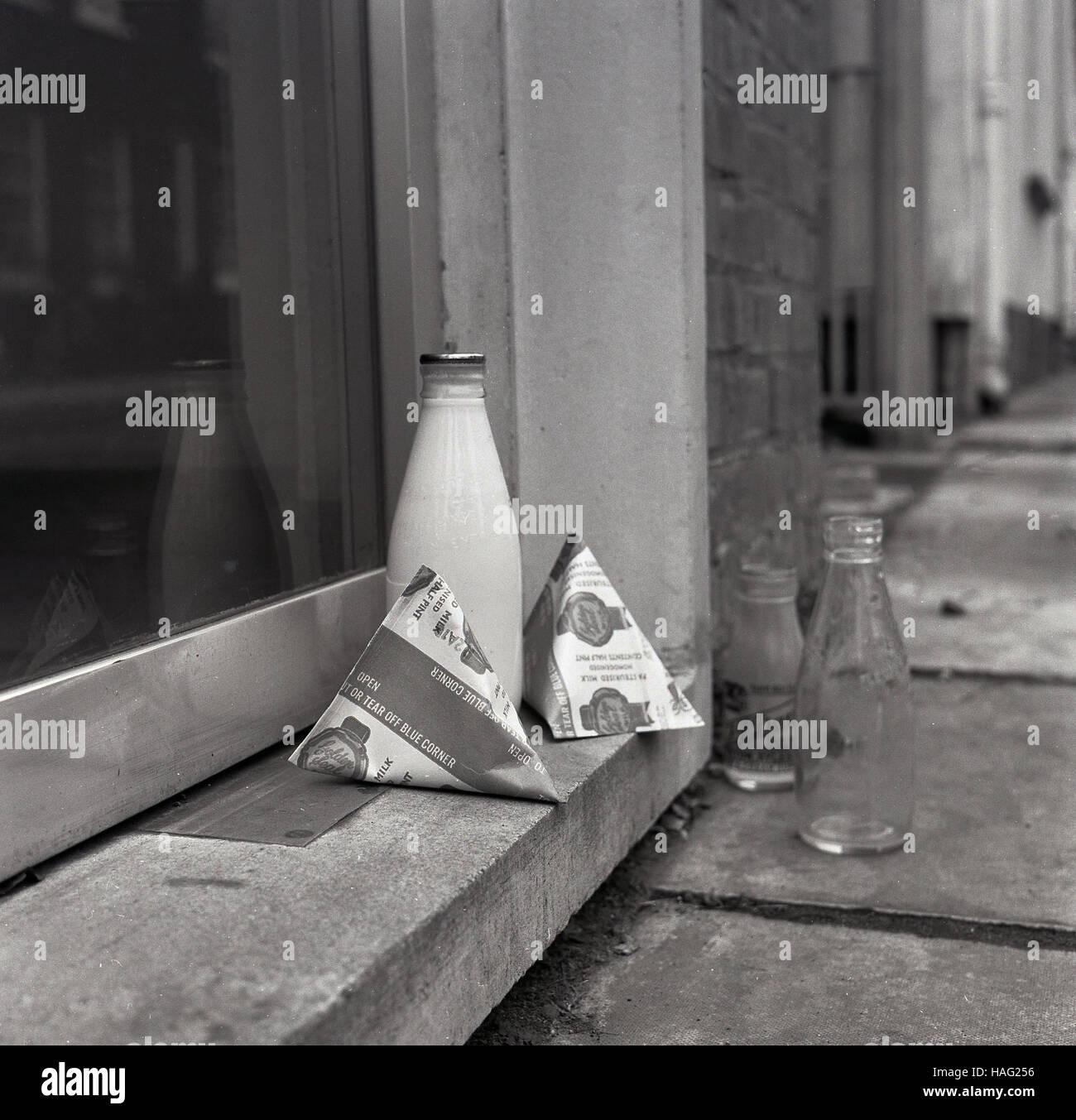 1965, histórico, una pinta de tamaño de botella de leche de vidrio y dos cartones de leche sentarse en Imagen De Stock