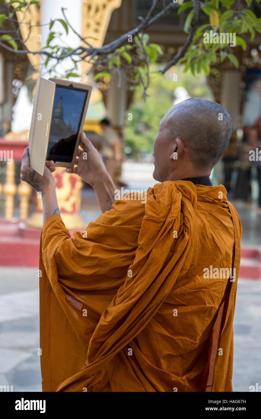 Un monje budista utilizando un ipad para fotografiar la Pagoda Kuthodew en Mandalay, Myanmar (Birmania). Foto de stock