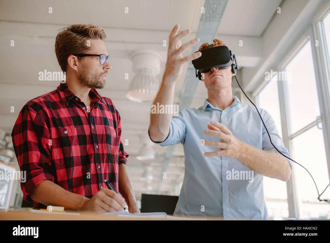 Foto de dos hombres jóvenes probando casco de realidad virtual. Los hombres de negocios y discutir las pruebas Imagen De Stock