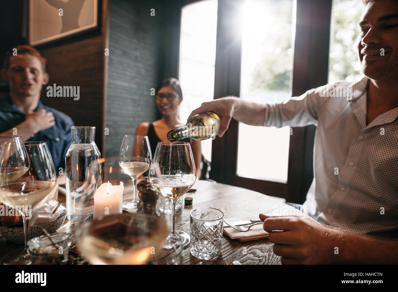 Grupo de amigos disfrutando de una comida con vino en un restaurante. Feliz joven vertiendo vino en vasos. Imagen De Stock